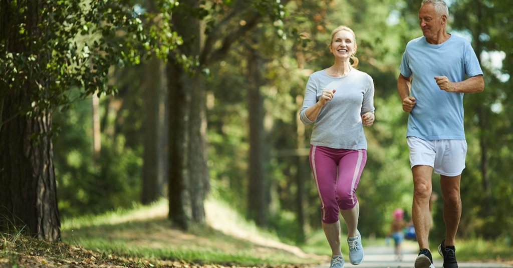Active and healthy aged couple running in natural environment on summer morning; blog: Everyday Habits to Keep Kidneys Healthy