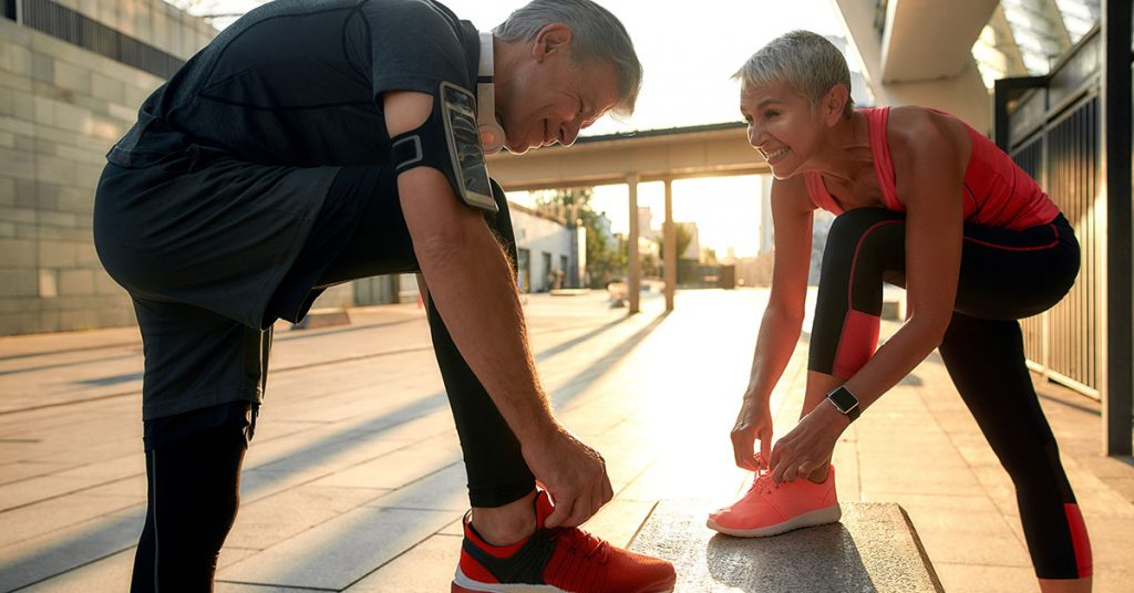 Healthy family. Active middle-aged couple in sports clothing tying shoelaces before jogging outdoors. Fit, fitness, exercise. Healthy lifestyle concept. Exercising together; blog: Safe Fitness Tips for Kidney Patients